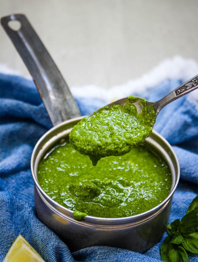 Fresh pesto sauce with a spoon to show smooth texture of the sauce