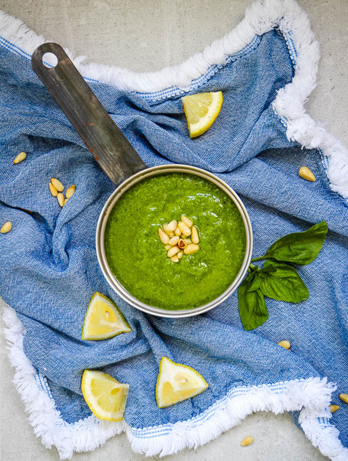 Fresh Pesto Sauce made in a blender in under 5 minutes is plated with pine nuts and sliced lemons.