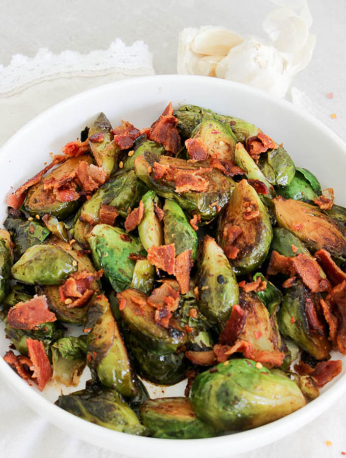 beer and bacon brussles sprouts plated in a white bowl, overhead shot