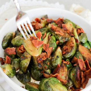 Pan roasted beer and bacon brussles sprouts, with a fork holding brussles sprout in a white bowl