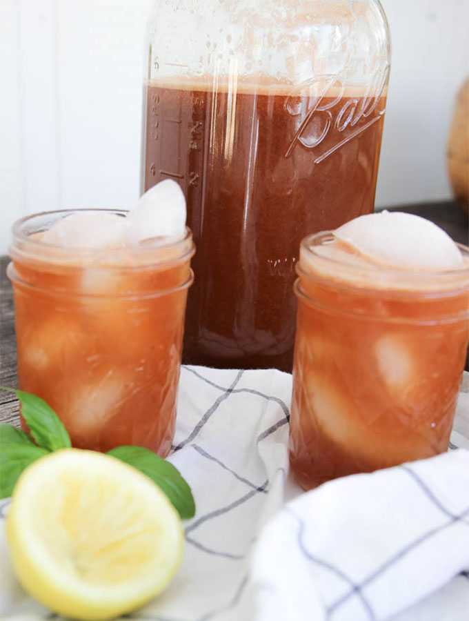 refined sugar free watermelon basil lemonade with two cups, a pitcher, fresh basil, and squeezed lemon with a napkin.