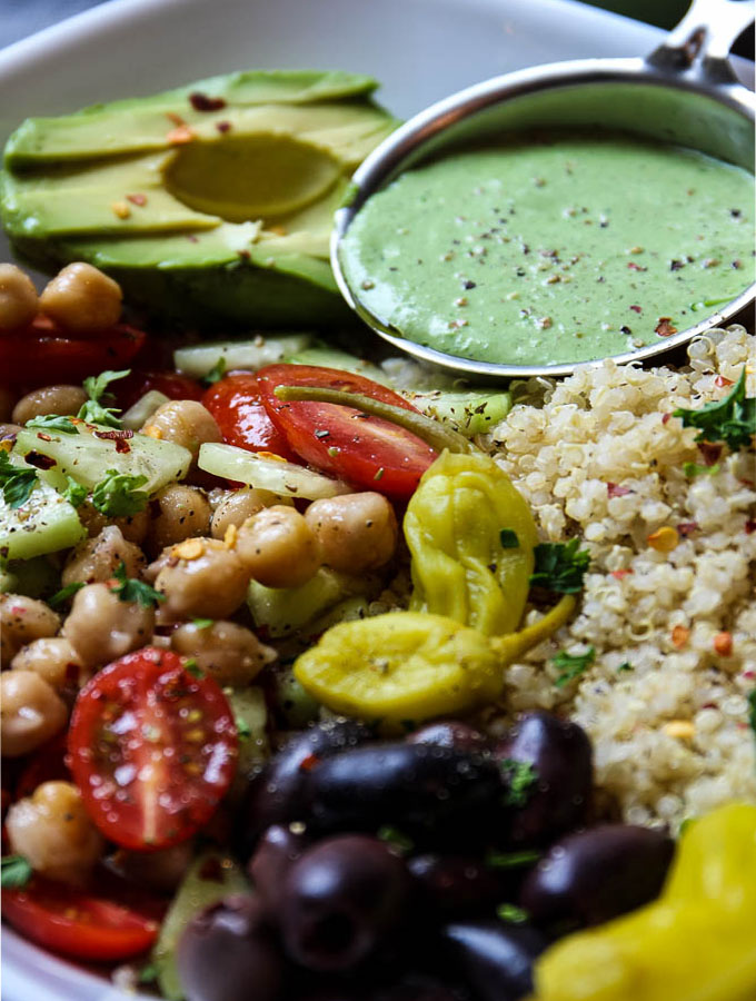 Mediterranean Quinoa Salad Bowl With Green Goddess Dressing in a little metal cup