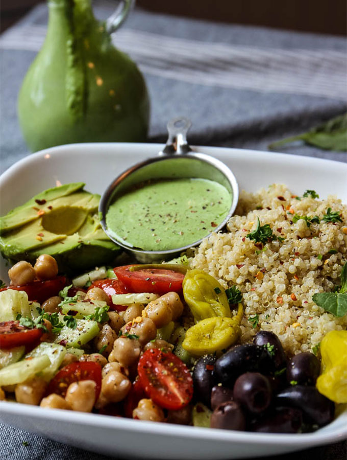 Mediterranean Quinoa Salad Bowl With Green Goddess Dressing in the background, dripping out of the bottle