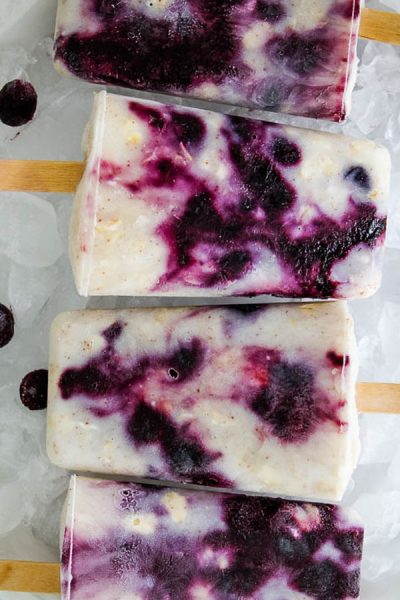 blueberry yogurt popsicles plated on a bowl of ice.