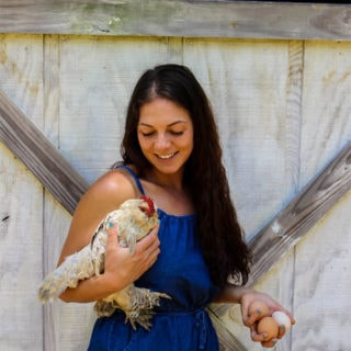 Sherry Brubaker holding fresh eggs and a chicken against a white barn door
