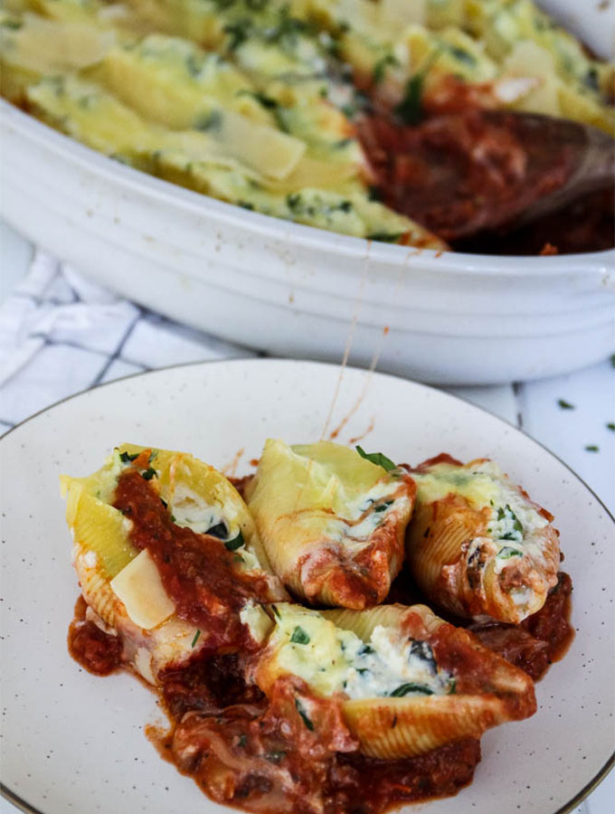 stuffed shells served on a white plate, with the main dish in the background