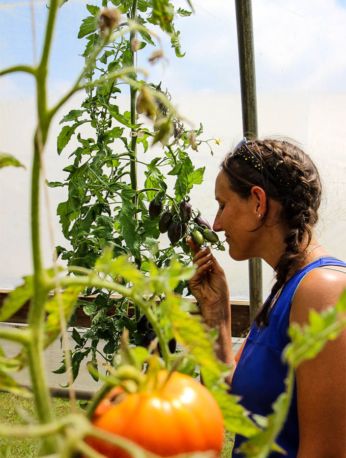 Bea Skinner, Farm Manager of crescere Farms, posing with her tomatoes