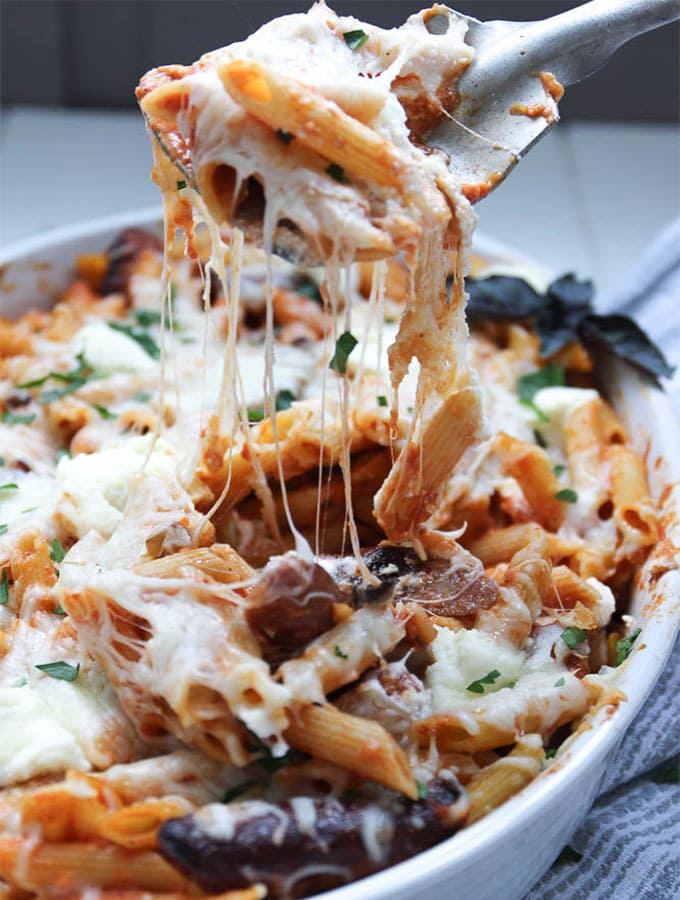 Penne pasta is scooped out of a large baking dish with cheese stringing from the spoon.