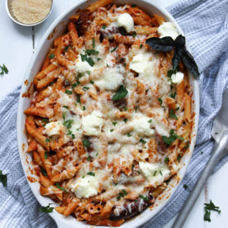 Baked penne pasta in a large dish with cheese, sausage, peppers, sauce, and ricotta.