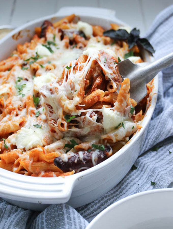 A large serving spoon is scooping out baked penne pasta from a large baking dish.