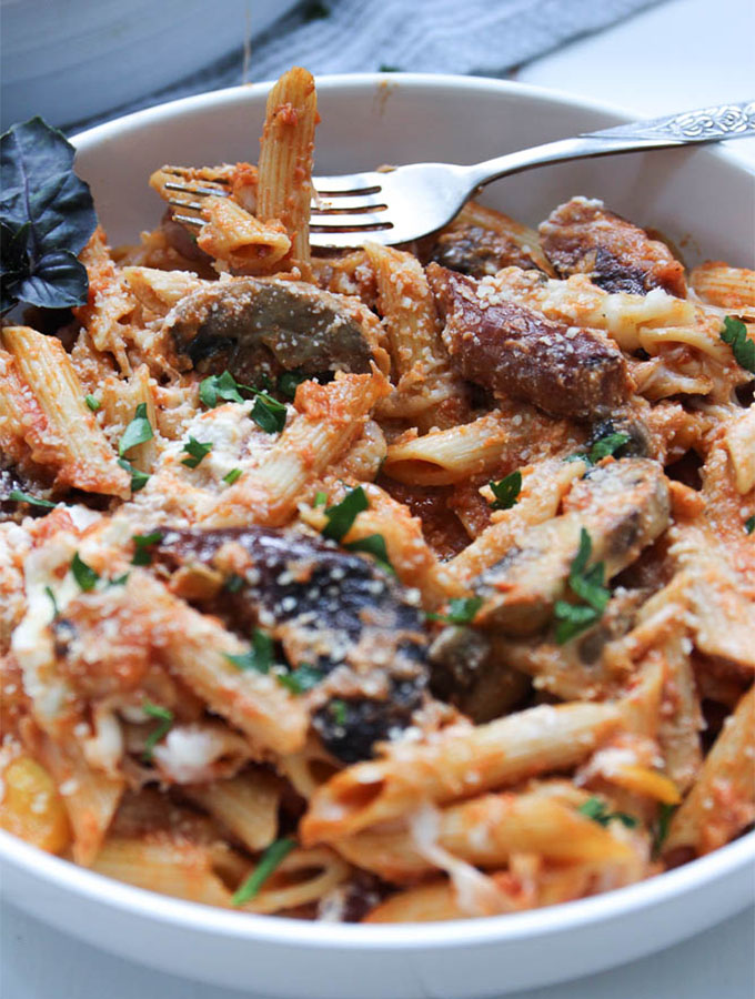 A fork is piercing baked penne that is topped with parmesan cheese, fresh parsley, and basil.
