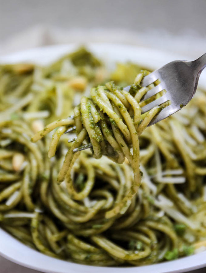pesto sauce over spaghetti pasta with a fork and twirled spaghetti.