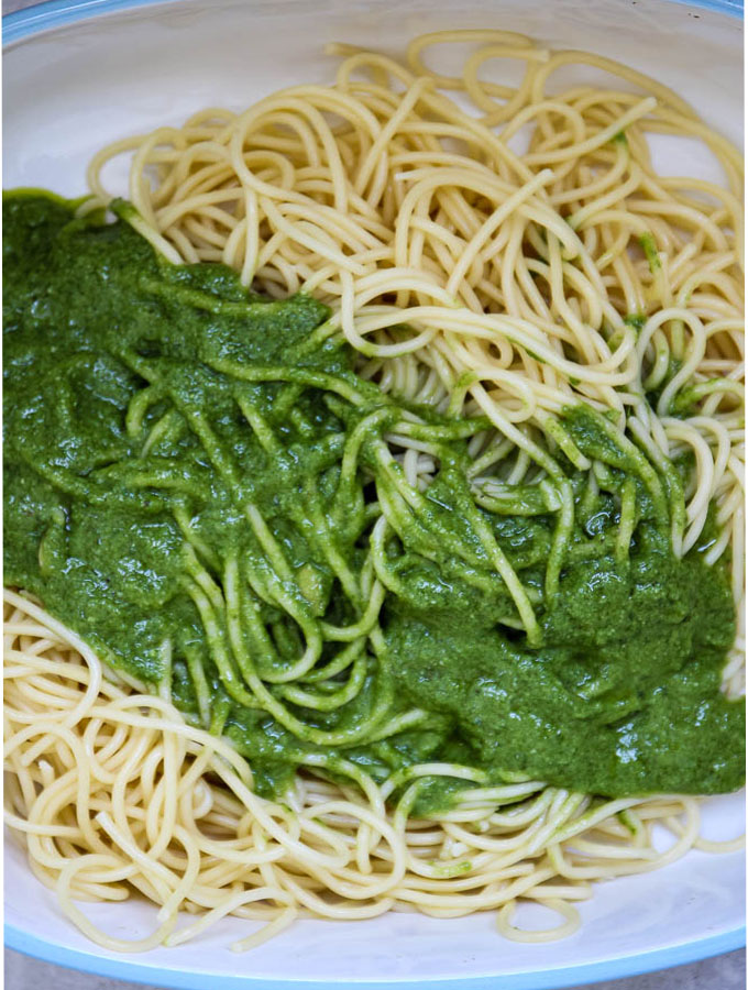pesto sauce over spaghetti pasta in a white bowl