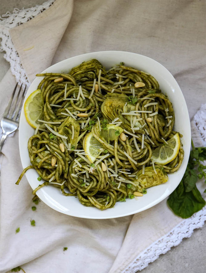 fresh made pesto over pasta with artichokes plated in a white bowl.