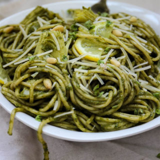 close up shot of pesto pasta with artichoke hearts with a fork and a white bowl