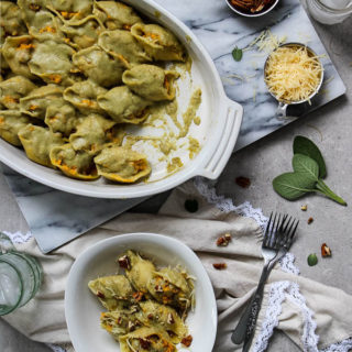 butternut squash stuffed shells with italian sausage and sage cream sauce is displayed with a smaller serving and sides like extra cheese sage, and pecans.
