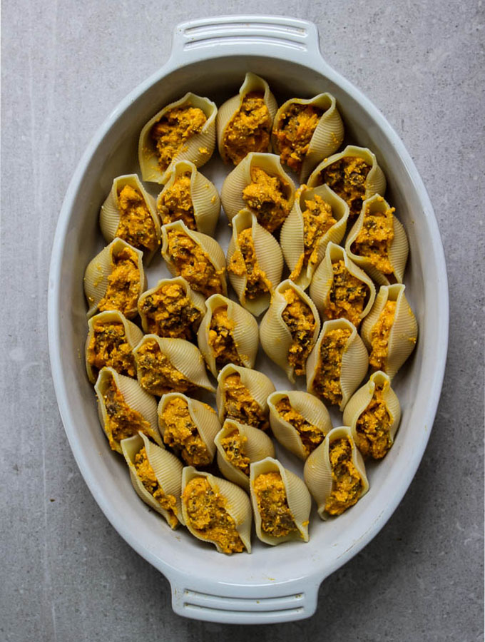 butternut squash stuffed shells with italian sausage and sage cream sauce in a white oven  safe dish before the sauce is added.