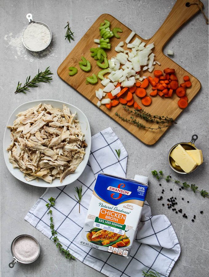 chicken and dumplings ingredients flat lay including chopped carrots, celery, garlc, butter, milk, chicken stock, etc.