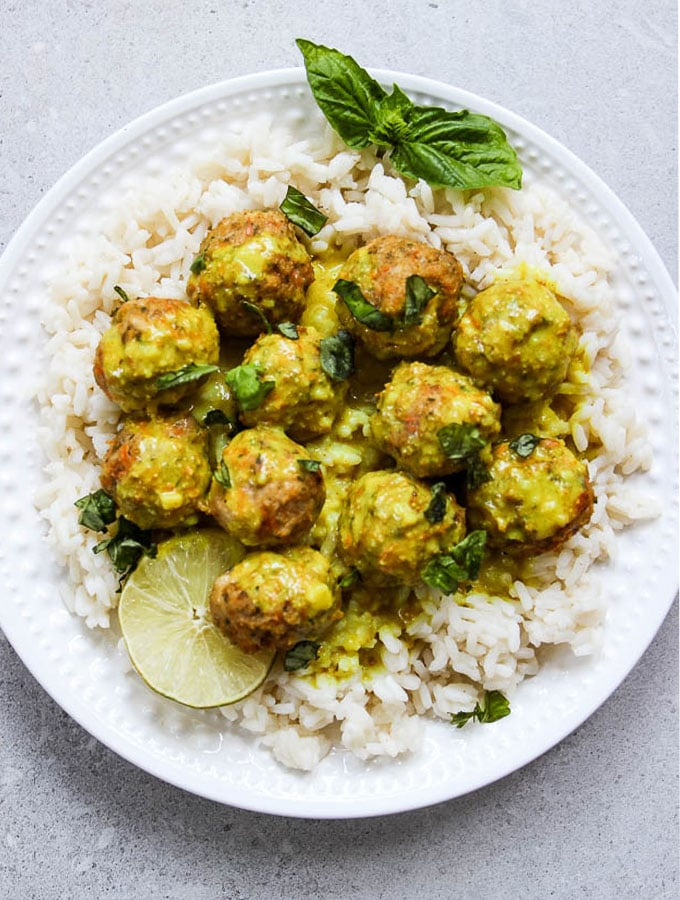 creamy coconut curry chicken meatballs flat lay shot on a white plate