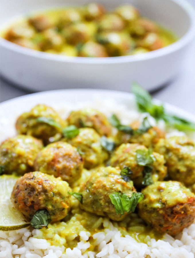 closeup of creamy coconut curry chicken meatballs over rice and topped with fresh herbs
