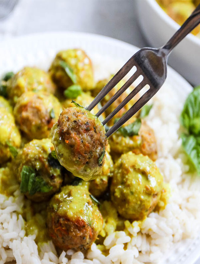 creamy coconut curry meatballs with a fork piercing a meatball