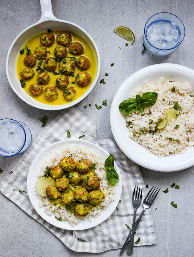 creamy coconut curry chicken meatballs flat lay shot with a skillet full of curry sauce and meatballs