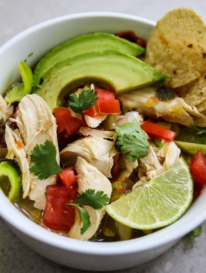 Mexican chicken and lime soup close up to show shredded chicken, bites of pepper, and the fixings like avocado slices and chips.