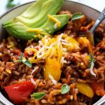 ustuffed bell pepper with ground beef skillet is plated with shredded cheese, avocado slices, and extra oregano in a white bowl.