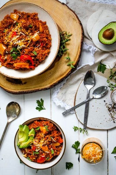 unstuffed pepper with ground beef skillet is plated with sides like avocado, herbs, and cheese.