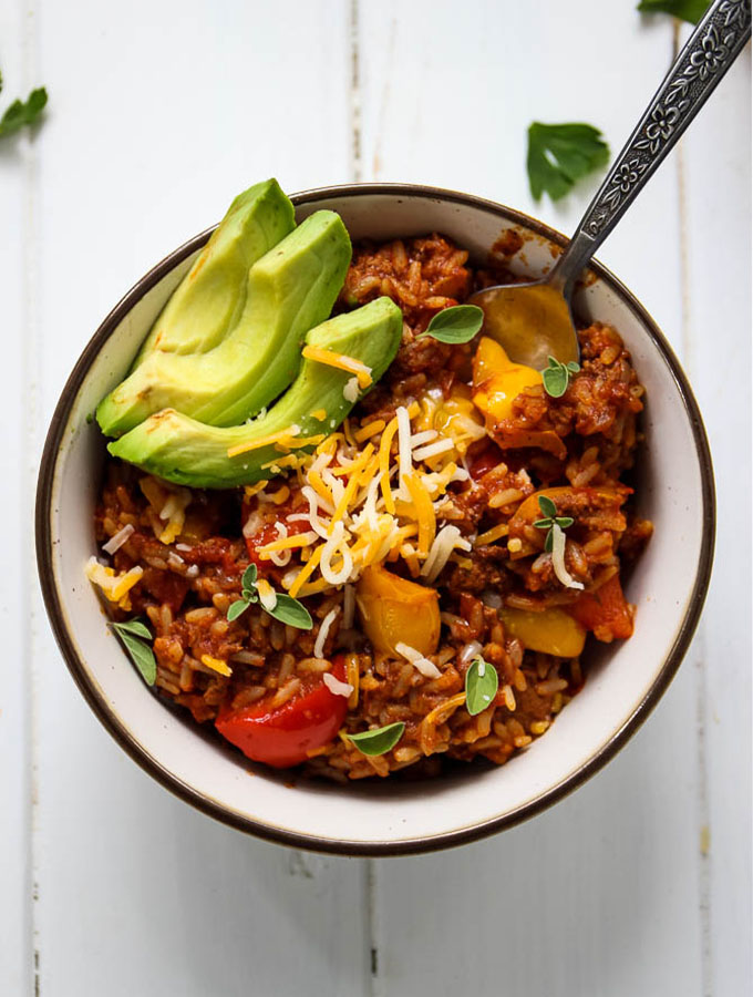 Unstuffed bell pepper skillet with ground beef plated in a white bowl with a spoon and fresh sides like avocado, cheese, and oregano.