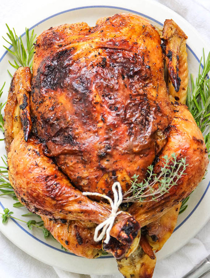 whole roasted herb and white wine chicken has crispy skin and juicy meat.