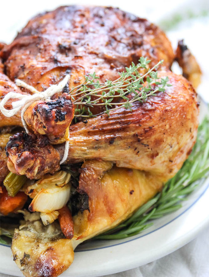 white wine and fresh herb roasted chicken stuffed with fresh carrots, celery and onion is served with more fresh herbs and plated on a white plate.