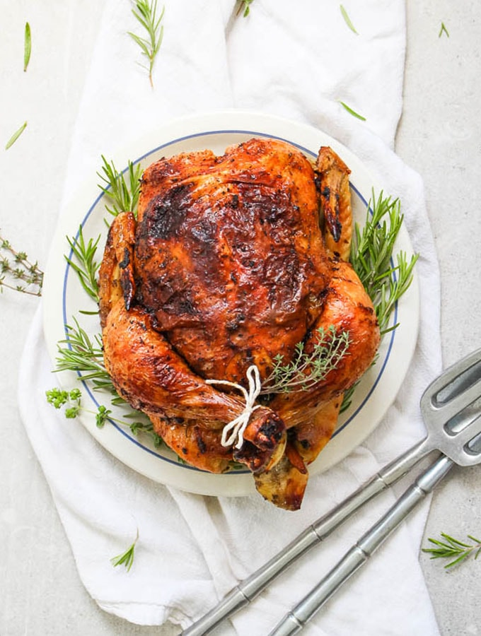white wine and fresh herb roasted whole chicken plated on a white plate