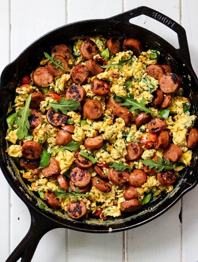 Breakfast Scramble with chicken sausage, spinach, arugula, bell peppers and scrambled eggs is easily cooked in a cast iron pan.