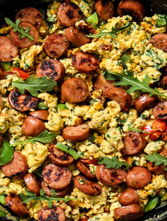 Cast iron skillet breakfast scramble has eggs, sausage, spinach, arugula bell peppers, and sun dried tomatoes.