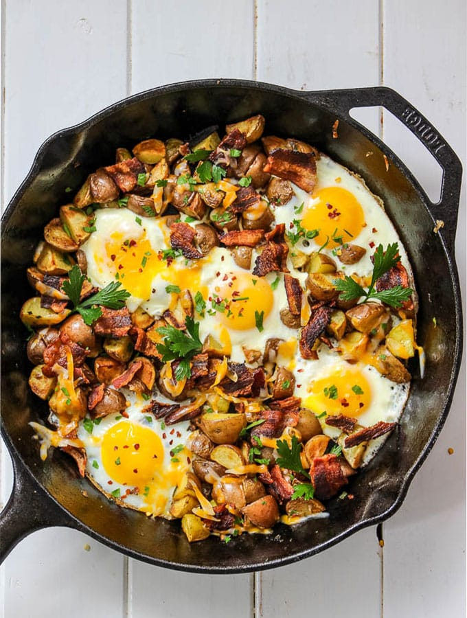 Cheesy egg, bacon, and potato skillet is made easily in a cast iron pan under thirty minutes.