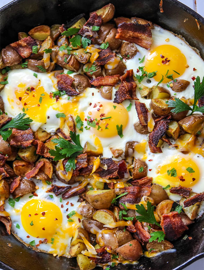 Cheesy egg bacon and potato skillet is in a black cast iron pan and topped with fresh parsley.