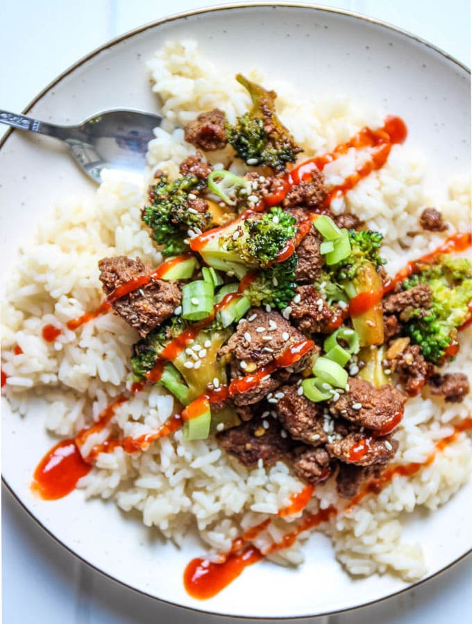 Easy 30 minute meal korean beef and broccoli rice bowl is topped with siracha sauce and sesame seeds.