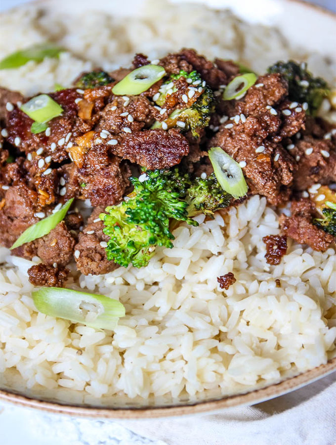 Korean beef and broccoli with rice is topped with sesame seeds and scallions.