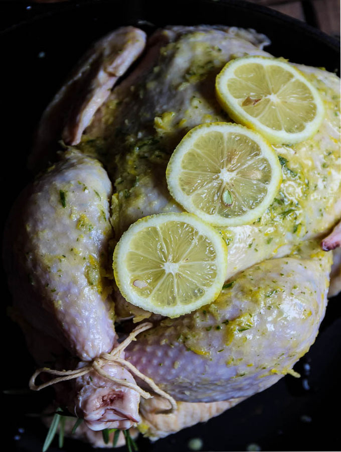 Lemon and herb roasted chicken is topped with a few sliced of fresh lemon before it goes into the oven to add a little extra flavor.