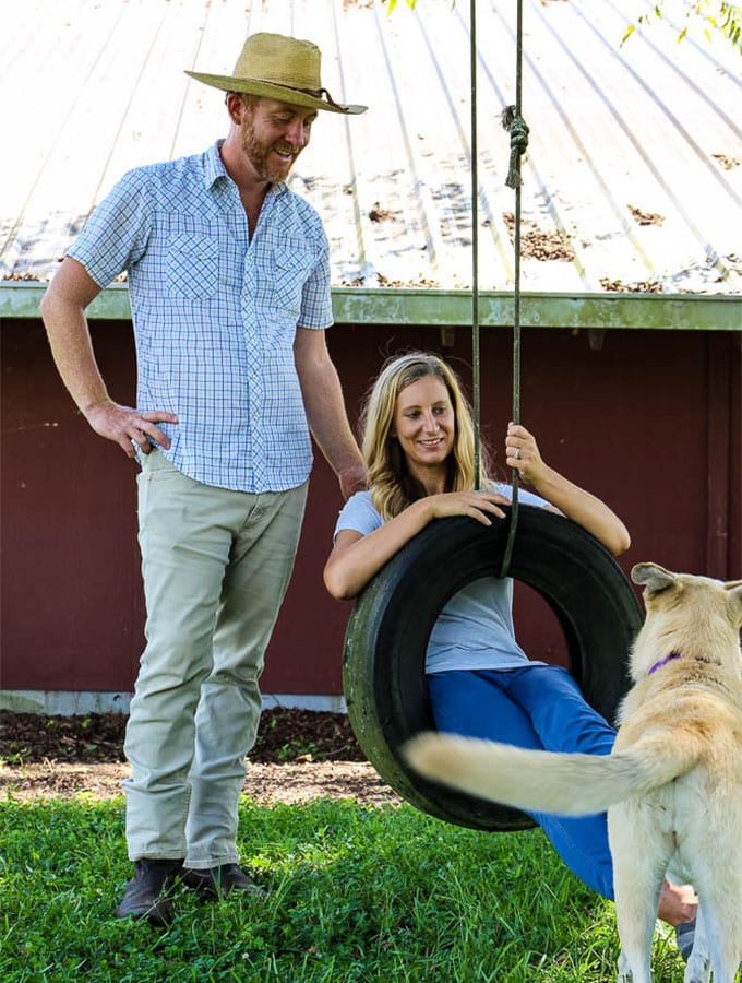 Meredith and Steven Elliott of Maeday farm are posed on a tire swing outside of their barn.
