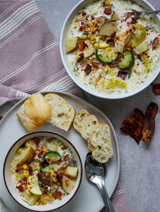 Corn and zucchini chowder is plated with a heaping bowl of hot soup and crusty bread.  It is topped with bits of bacon and paprika.