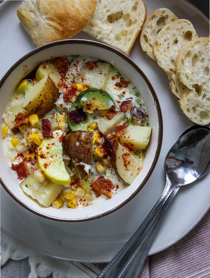 Corn and zucchini chowder is served in a white bowl with crusty bread.