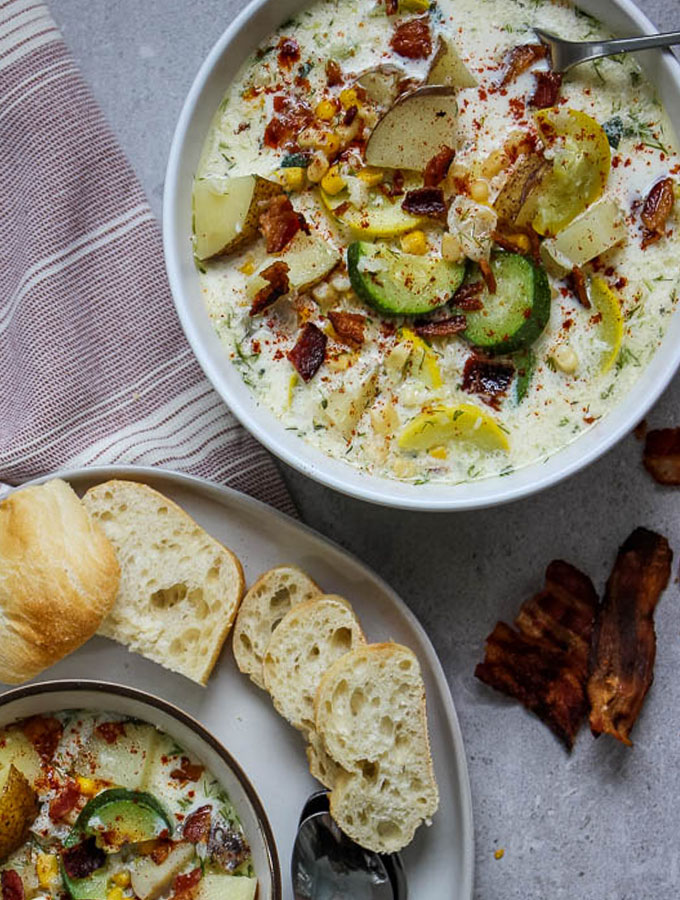 Corn and Zucchini chowder is pated in a white bowl and topped with a dash of paprika powder.