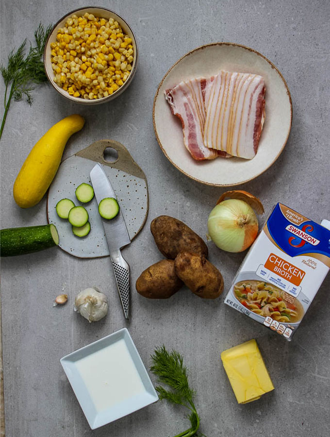 Corn and Zucchini chowder ingredients include chicken broth, half and half, bacon, corn, zucchini, summer squash, russet potatoes, and fresh herbs.
