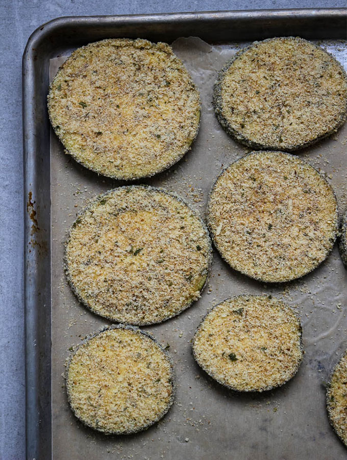 Crispy eggplant slices are in the rpocess of being made. They are breaded and plated on a parchment paper lined baking sheet.