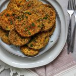 Crispy eggplant slices are plated on a gray plate with fresh parsley and a couple of forks.