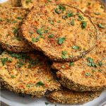 Baked eggplant slices are plated on a white plate and topped with fresh parsley to show texture.