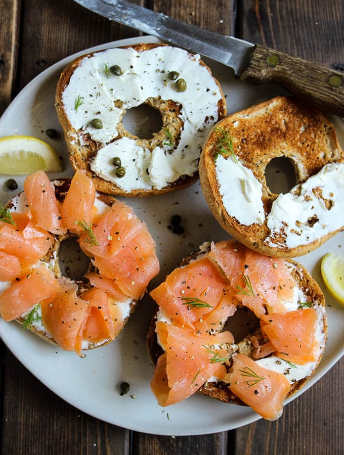 Lox of bagels is made with cream cheese, bagels, and smoked salomon with bits of fresh dill, capers, and a cucumber sauce.