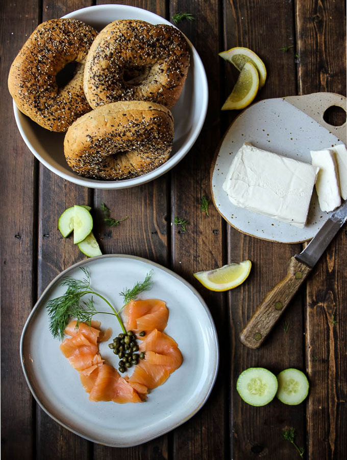 Lox and bagels ingredients include bagels, cream cheese, smoked salmon, capers, cucumbers, and lemons.